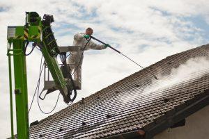 Čištění střechy proudem horké vody při šetrném tlaku na střeše nového domu.