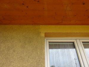 Detailní náhled postupného čištění zdi rodinného domu na špatně dostupném místě.