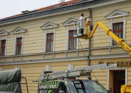 Mytí fasády staršího domu z výškové plošiny.