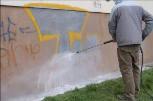 Průběh ostraňování graffiti na spodní části panelového domu speciální technikou, kterou má firma Umyjemto k dispozici.