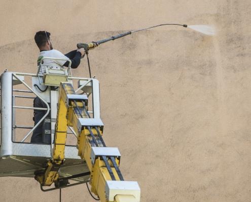 Bezdotyková aplikace a čištění fasády - Profesionál z Umyjemto myje znečištěnou fasádu za pomocí zvdihací plošiny